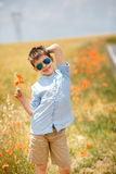 Cute smiling boy holding bouquet of poppies Stock Photography