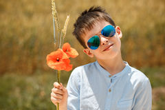 Cute smiling boy holding bouquet of poppies Royalty Free Stock Images