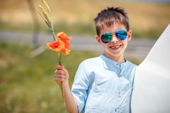 Cute smiling boy holding bouquet of poppies outdoors Stock Images