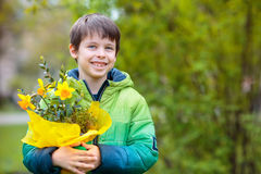 Cute smiling boy holding daffodils Stock Images