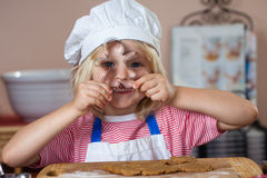 Cute smiling boy peeking through cookie cutter Royalty Free Stock Photos