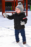 Cute  smiling boy playing with snow Stock Image
