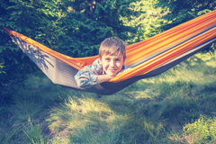 Cute smiling boy is swinging in a hammock in a forest glade Stock Image