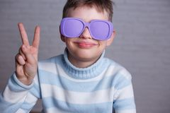 Cute smiling boy in violet sunglasses with opaque lenses showing stock photography