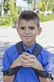 Cute brunette boy eleven years old. Cute smiling brunette boy with school backpack stock photo