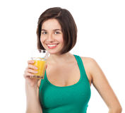 Cute smiling brunette drinking an orange juice Royalty Free Stock Image