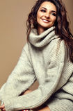 Cute smiling brunette woman girl in casual hipster warm gray sweater Royalty Free Stock Photography