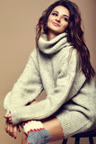 Cute smiling brunette woman girl in casual hipster warm gray sweater Royalty Free Stock Image