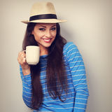 Cute smiling casual woman in straw hat holding cup of tea and lo. Oking. Toned closeup portrait Stock Photography