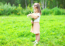 Cute smiling child with bouquet chamomiles flowers in summer Royalty Free Stock Photo
