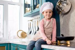 cute smiling child in chef hat and apron looking at frying pan stock images