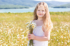 Cute smiling child girl at camomile field Royalty Free Stock Photography