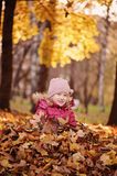 Cute smiling child girl having fun on the autumn walk and sitting in leaves Royalty Free Stock Image