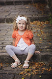 Cute smiling child girl in orange cardigan sitting on stone road with steps in warm autumn day Royalty Free Stock Photo