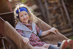 Cute smiling child girl in spring garden sitting in wheelbarrow Stock Images