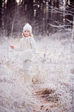 Cute smiling child girl on the walk in winter frozen forest Royalty Free Stock Photos