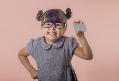Cute smiling child with glasses holding bank card in her hands. Kid with credit card. Little girl showing empty blank paper note copy space stock photo