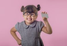 Cute smiling child with glasses holding bank card in her hands. Kid with credit card. Little girl showing empty blank paper note copy space royalty free stock images