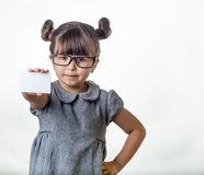 Cute smiling child with glasses holding discount white card in her hands. Kid with credit card. Little girl showing empty blank paper note copy space royalty free stock photography