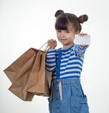 Cute smiling child holding discount white card and shopping bags in her hands. Kid with credit card. Little girl showing empty bl stock photography