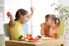 Cute smiling child and toddler girls playing and eating spaghetti with vegetables for healthy lunch sitting in a white sunny kitch. Cute smiling child and kid royalty free stock photos