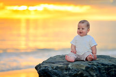 Cute smiling child sitting on the rock Stock Images