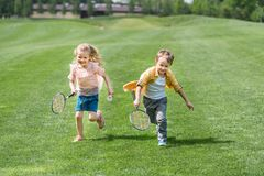 Cute smiling children with badminton rackets running together. In park stock image