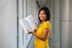 Cute Smiling College Girl Open Textbook. A cute college student smiles and holds a textbook open on a modern university campus.  Young female Asian Thai model Stock Photos