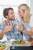 Cute smiling couple enjoying white wine over a meal together Stock Photo