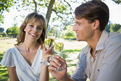 Cute smiling couple sitting outside toasting with champagne Stock Image