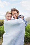 Cute smiling couple standing outside wrapped in blanket Stock Image