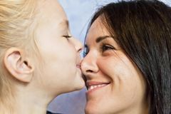 Blond daughter with brunette mother. Cute smiling daughter kissing her mother to nose royalty free stock images