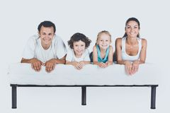 Cute Smiling Family Lying on Orthopedic Mattress. Isolated on White Background. Healthy, Family Concept stock images