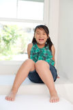 Cute smiling girl. Cute girl sitting on window and smiling Royalty Free Stock Photo