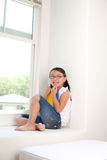 Cute smiling girl. Sitting on window and posing to camera royalty free stock images