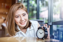 Cute smiling girl with alarm clock on wooden table Royalty Free Stock Images