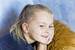 Cute white girl with blond hair. Cute smiling girl with blond hair on blue background royalty free stock photography