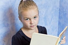 Cute white girl with blond hair. Cute smiling girl with blond hair are reading a book stock photos