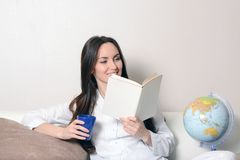 Cute smiling girl with a blue Cup and the diary, sitting on the couch in the room and reads. Cute smiling girl with a blue Cup and the diary, sitting on the Stock Images