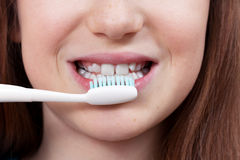 Cute smiling girl brushing her teeth. Cute smiling girl with permanent and milk teeth brushing her teeth. Dental hygiene Royalty Free Stock Photos