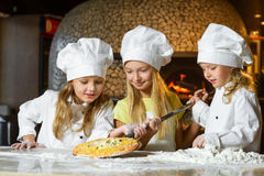 Cute smiling girl chef admiring look at pizza Stock Photo