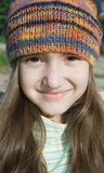 Cute smiling girl in colored knitted hat Stock Image