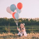 Cute smiling girl with colorful balloons. Cute smiling girl in white dress with colorful balloons crouching in the grass - Retro look Royalty Free Stock Photo