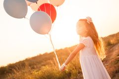 Cute smiling girl with colorful balloons at sunset. Cute smiling girl in white dress with colorful balloons smiling and playing on meadow at sunset Royalty Free Stock Images