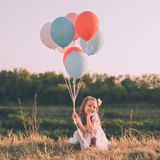 Cute smiling girl with colorful balloons. Cute smiling girl in white dress with colorful balloons crouching in the grass. Square composition Royalty Free Stock Images