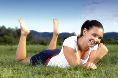 Cute smiling girl with a daisy. In her hand, lying on the grass in the park on the sunny summer evening - Glamour effect Stock Photos