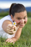 Cute smiling girl with a daisy. In her hand, lying on the grass in the park on the sunny summer evening - Glamour effect Royalty Free Stock Image