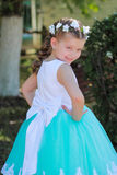 Cute smiling girl dressed in blue and white dress with a wreath of artificial flowers on her head, child in a festive dress on a n. Ature background, half-turn Royalty Free Stock Photo