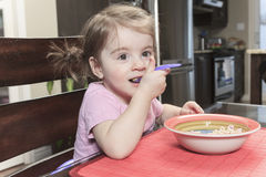 Cute smiling girl eating cereal with the milk in Stock Images