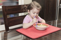 Cute smiling girl eating cereal with the milk in Royalty Free Stock Images